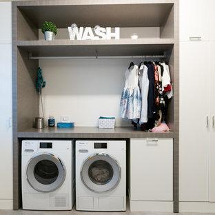 Inspiration för mellanstora moderna linjära grått grovkök, med en nedsänkt diskho, släta luckor, vita skåp, laminatbänkskiva, vita väggar, klinkergolv i porslin, en tvättmaskin och torktumlare bredvid varandra och grått golv