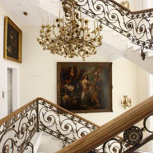 Foto på en stor vintage u-trappa i marmor, med sättsteg i marmor och räcke i flera material