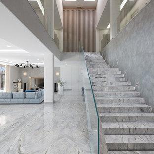 На фото: прямая лестница в современном стиле с стеклянными перилами с