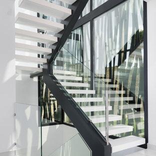 Стильный дизайн: п-образная лестница в стиле модернизм с стеклянными перилами без подступенок - последний тренд