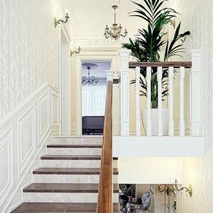 Diseño de escalera en U, tradicional, de tamaño medio, con escalones con baldosas, contrahuellas con baldosas y/o azulejos y barandilla de madera