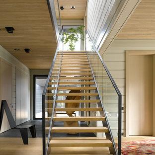 Пример оригинального дизайна интерьера: прямая лестница в современном стиле с деревянными ступенями и перилами из смешанных материалов без подступенок