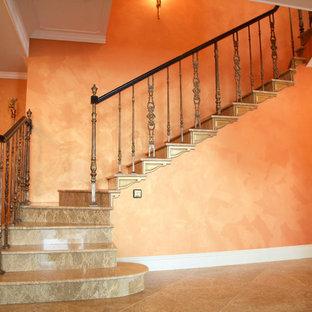 Modelo de escalera en L, mediterránea, grande, con escalones de mármol, contrahuellas de mármol y barandilla de madera