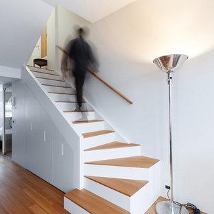 Ejemplo de escalera curva, contemporánea, pequeña, con escalones de madera, barandilla de madera y contrahuellas de madera pintada