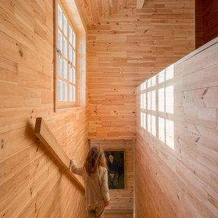 На фото: большая прямая лестница в стиле кантри с деревянными ступенями, деревянными подступенками и деревянными перилами