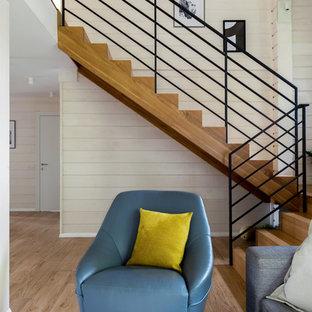 На фото: п-образная лестница среднего размера в скандинавском стиле с деревянными ступенями, деревянными подступенками и металлическими перилами
