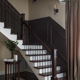 На фото: угловая лестница в классическом стиле с деревянными ступенями, крашенными деревянными подступенками и перилами из смешанных материалов