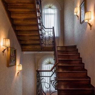 Пример оригинального дизайна интерьера: большая п-образная лестница в классическом стиле с деревянными ступенями и деревянными подступенками