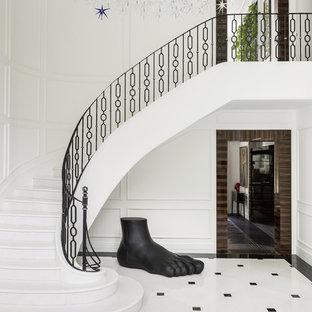 На фото: изогнутая лестница в стиле современная классика с крашенными деревянными ступенями и крашенными деревянными подступенками с