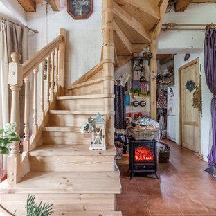 На фото: изогнутая лестница в стиле кантри с деревянными ступенями, деревянными подступенками и деревянными перилами с