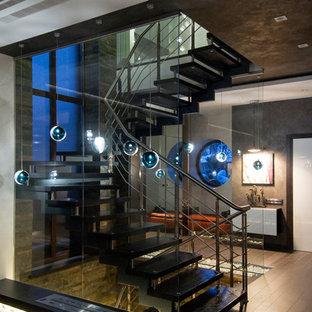Cette image montre un escalier sans contremarche courbe design de taille moyenne avec un garde-corps en métal.