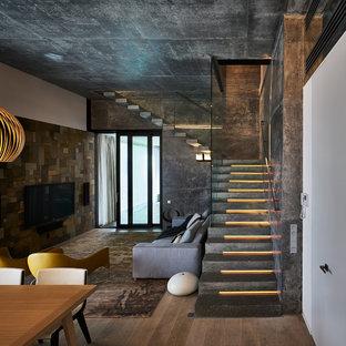 На фото: угловая лестница среднего размера в современном стиле с ступенями из сланца, подступенками из сланца и стеклянными перилами с