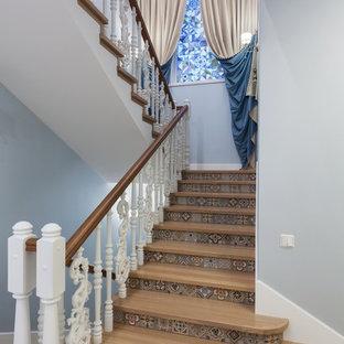 Стильный дизайн: п-образная лестница в средиземноморском стиле с деревянными ступенями, подступенками из плитки и деревянными перилами - последний тренд