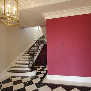 Ejemplo de escalera en U, tradicional, grande, con escalones de mármol, contrahuellas de madera y barandilla de metal