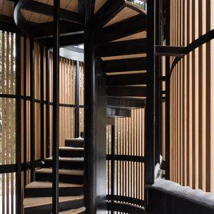 На фото: винтовая лестница в современном стиле с деревянными ступенями, металлическими подступенками и металлическими перилами с