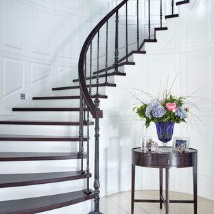 На фото: изогнутая лестница в стиле неоклассика (современная классика) с деревянными ступенями и перилами из смешанных материалов с