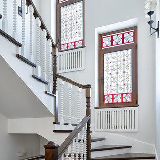 На фото: изогнутая лестница в современном стиле с деревянными ступенями и деревянными перилами