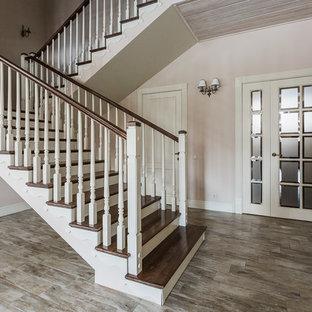 На фото: прямая лестница среднего размера в классическом стиле с деревянными ступенями, деревянными подступенками, деревянными перилами и обоями на стенах