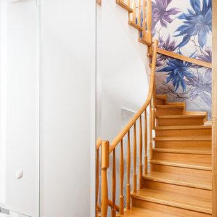 На фото: изогнутая лестница в скандинавском стиле с деревянными ступенями, деревянными подступенками и деревянными перилами с