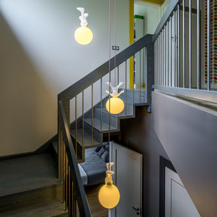 На фото: большая угловая лестница в скандинавском стиле с деревянными ступенями, деревянными подступенками и перилами из смешанных материалов