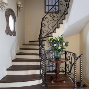 Пример оригинального дизайна: изогнутая лестница в современном стиле с деревянными ступенями и металлическими перилами