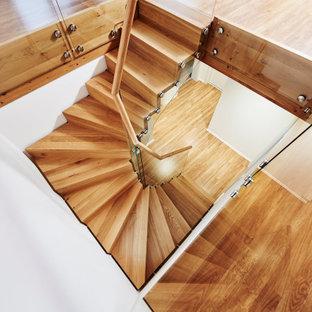На фото: изогнутая лестница в скандинавском стиле с деревянными ступенями, деревянными подступенками и перилами из смешанных материалов