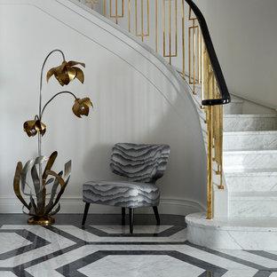 Пример оригинального дизайна интерьера: изогнутая лестница в стиле современная классика с мраморными ступенями, подступенками из мрамора и перилами из смешанных материалов
