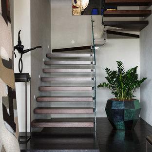 На фото: п-образная лестница в современном стиле с деревянными ступенями и стеклянными перилами без подступенок