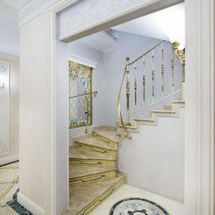 Свежая идея для дизайна: изогнутая лестница в классическом стиле с мраморными ступенями и металлическими перилами - отличное фото интерьера