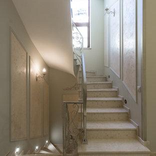 Пример оригинального дизайна интерьера: большая изогнутая лестница в классическом стиле с мраморными ступенями, подступенками из мрамора и металлическими перилами