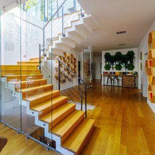 Удачное сочетание для дизайна помещения: угловая лестница в стиле фьюжн с деревянными ступенями, деревянными подступенками и металлическими перилами - самое интересное для вас