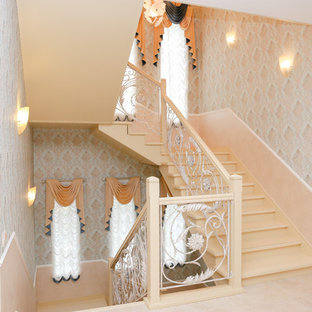 Modelo de escalera curva y papel pintado, clásica renovada, grande, con escalones de madera pintada, contrahuellas de madera pintada, barandilla de metal y papel pintado