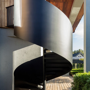 Новый формат декора квартиры: винтовая лестница в современном стиле с металлическими ступенями и металлическими перилами без подступенок