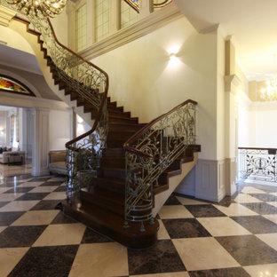 Diseño de escalera en U y panelado, tradicional renovada, grande, con escalones de madera, contrahuellas de madera, barandilla de metal y panelado