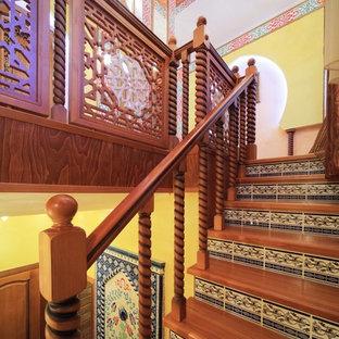 Foto de escalera en L, asiática, con escalones de madera, contrahuellas con baldosas y/o azulejos y barandilla de madera