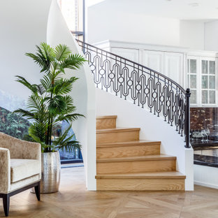 Пример оригинального дизайна: большая винтовая лестница в современном стиле с деревянными ступенями, деревянными подступенками и металлическими перилами