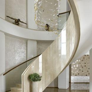 モスクワの大きい大理石のコンテンポラリースタイルのおしゃれなサーキュラー階段 (大理石の蹴込み板、混合材の手すり) の写真