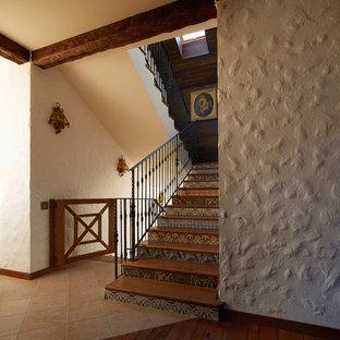 На фото: п-образные лестницы в стиле кантри с деревянными ступенями, подступенками из плитки и металлическими перилами