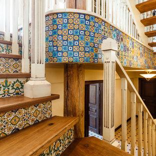 Пример оригинального дизайна: изогнутая лестница в стиле кантри с деревянными ступенями, подступенками из плитки и деревянными перилами