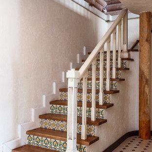 Ejemplo de escalera en L, de estilo de casa de campo, con escalones de madera, contrahuellas con baldosas y/o azulejos y barandilla de madera
