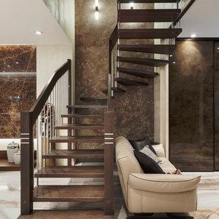На фото: большая изогнутая лестница в современном стиле с деревянными ступенями и перилами из смешанных материалов без подступенок с