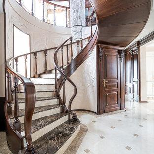 Свежая идея для дизайна: изогнутая лестница в классическом стиле с мраморными ступенями и деревянными перилами - отличное фото интерьера