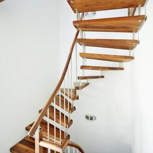 Ispirazione per una scala curva scandinava con pedata in legno e parapetto in legno
