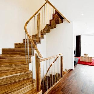 На фото: изогнутая лестница в современном стиле с деревянными ступенями, деревянными подступенками и перилами из смешанных материалов с