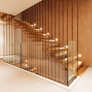 На фото: большая угловая лестница в современном стиле с деревянными ступенями и металлическими перилами без подступенок с