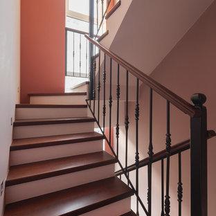 Modelo de escalera en U, ecléctica, de tamaño medio, con escalones de madera pintada, contrahuellas de hormigón y barandilla de metal