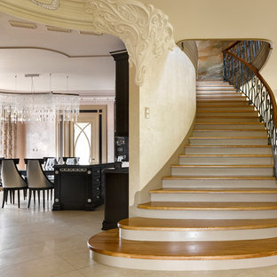 Идея дизайна: изогнутая лестница в стиле неоклассика (современная классика) с деревянными ступенями и перилами из смешанных материалов