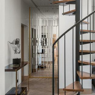 На фото: винтовая лестница в современном стиле с деревянными ступенями и металлическими перилами без подступенок с