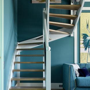 Ejemplo de escalera curva, contemporánea, sin contrahuella, con escalones de madera y barandilla de madera