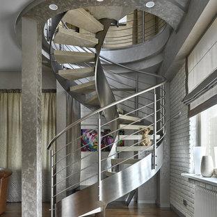 Inredning av en industriell svängd trappa, med öppna sättsteg och räcke i metall
